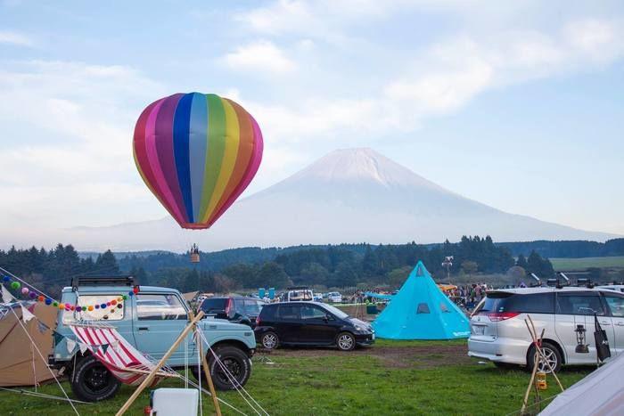 賑やかなキャンプ場とカラフルな気球と富士山