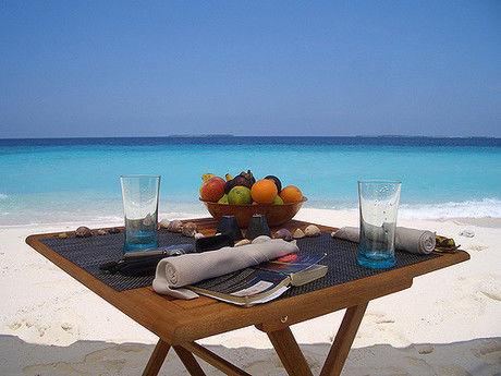 砂浜に置かれた折りたたみのウッドテーブル