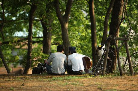 野外でギターを引く2人の男性