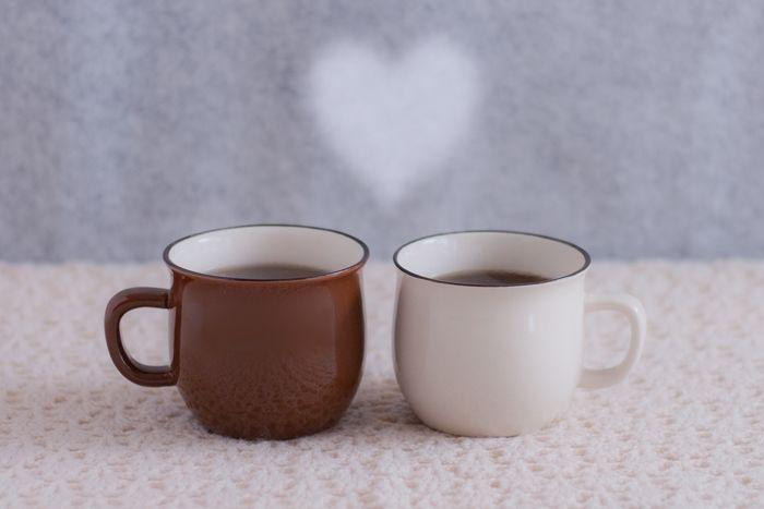 茶色と白色のマグカップに入れたコーヒー