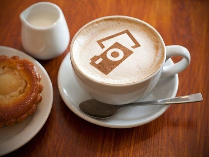 カメラと写真のラテアートが施されたコーヒーと焼き菓子
