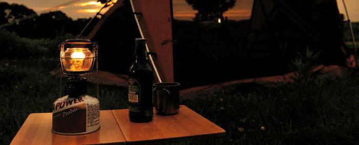 夜のキャンプ場でテーブルの上に置かれたランタン