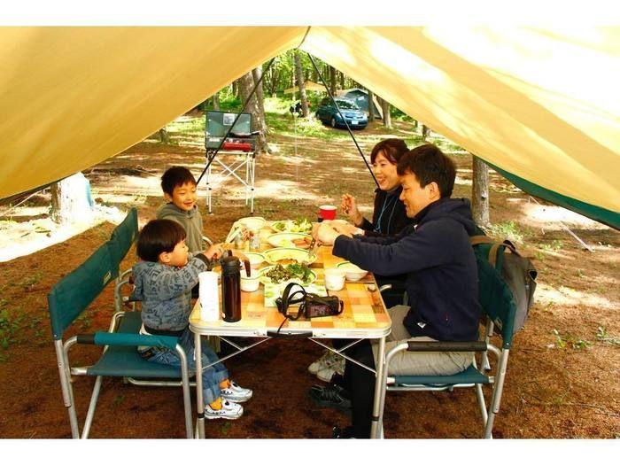 キャンプで食卓を囲む家族