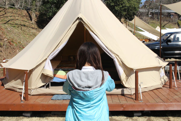 テント内の写真を外から撮る女性