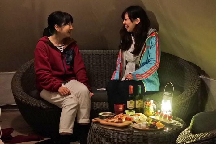 テント内の椅子でおしゃべりする女性