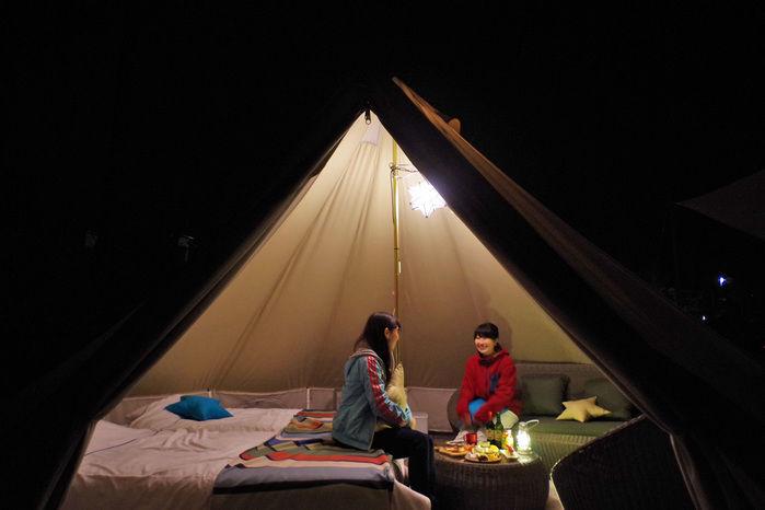 ベル型テントでグランピングを楽しむ女性