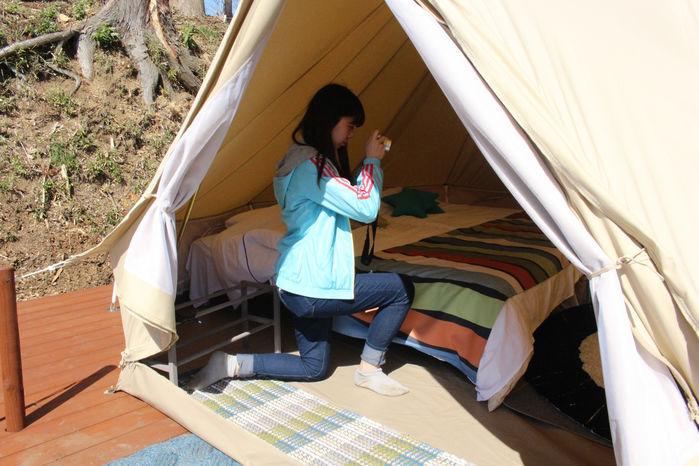 テント内の写真を撮る女性