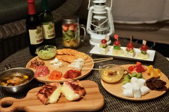 キャンプのテーブル上のおしゃれな食材やワイン