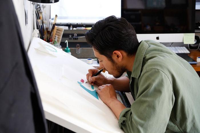 デザイナーがキャンバスに絵を描く様子