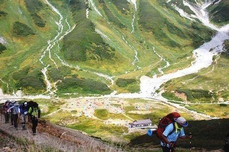 雷鳥沢キャンプ場の山々と小さく見えるカラフルなテントをせに山登りする人々