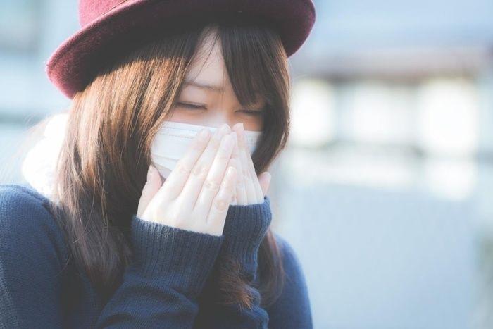 マスクをしてくしゃみをする女性