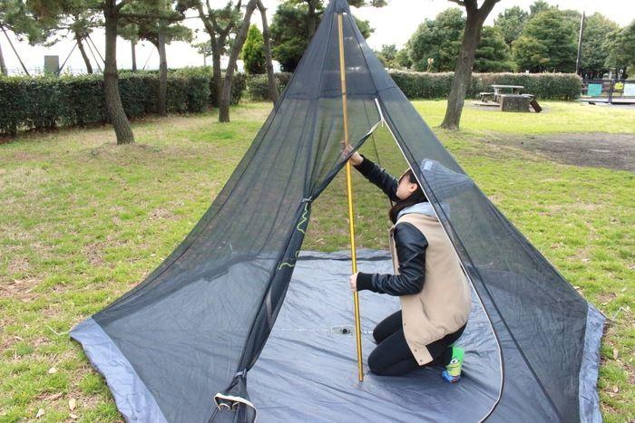 一人でテントを設営する女性