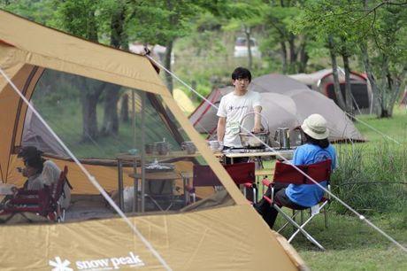 スノーピークのキャンプギアでキャンプを楽しむ人々