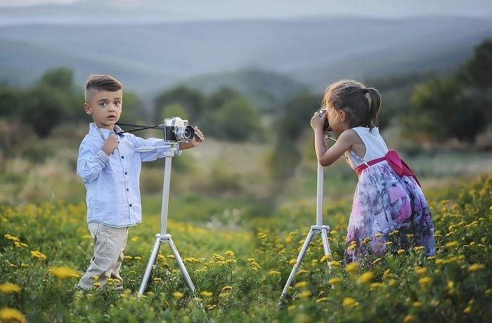 お花畑でカメラで写真を撮る子供たち