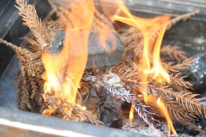 着火した炭とお米の袋と落ち葉