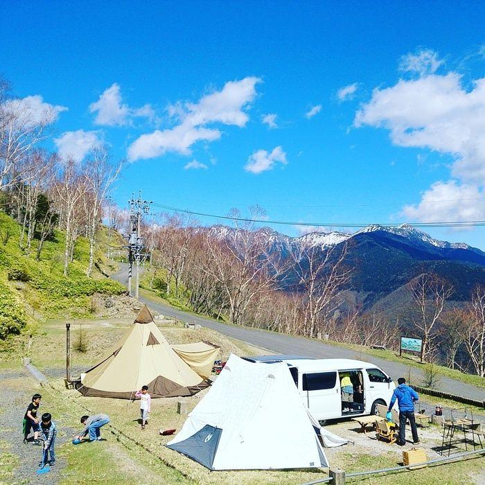 見晴らしのいい高原山岳オートキャンプ場でキャンプを楽しむ家族