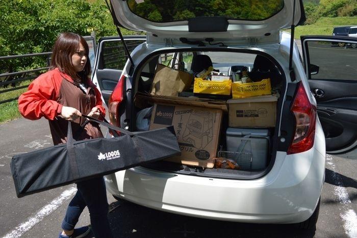 トランクに荷物をのせる女性