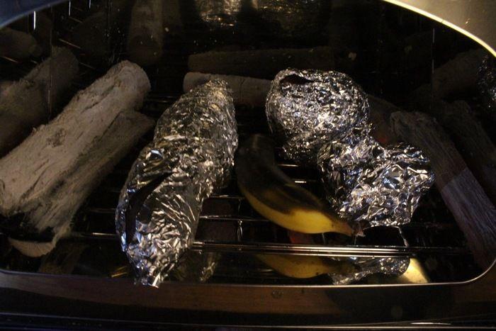 かまどで丸ごと野菜を焼く様子
