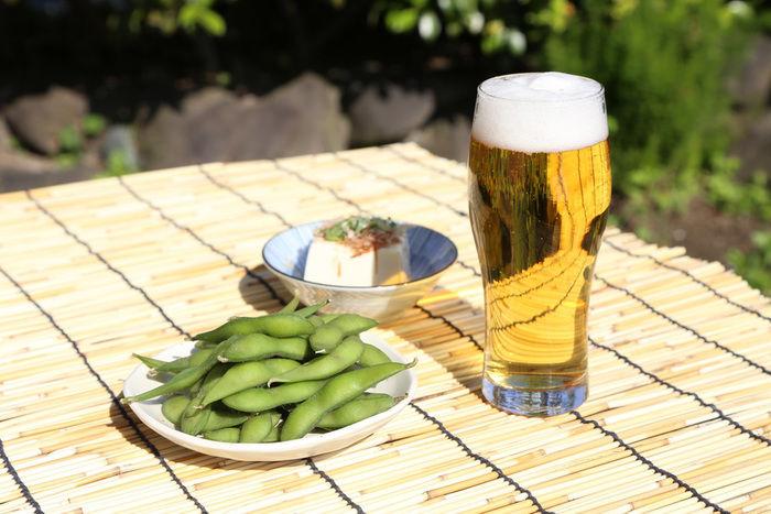 机に並べられたビールと冷奴と枝豆