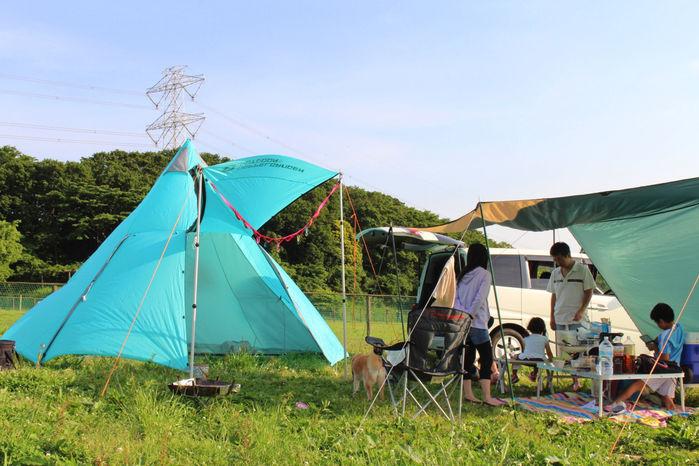 水色のティピーテントを使用する家族