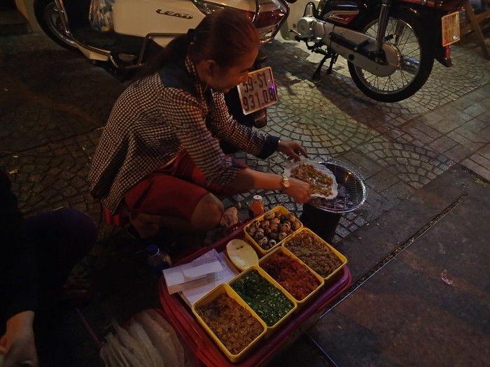 路面でピザを焼いているベトナム人女性