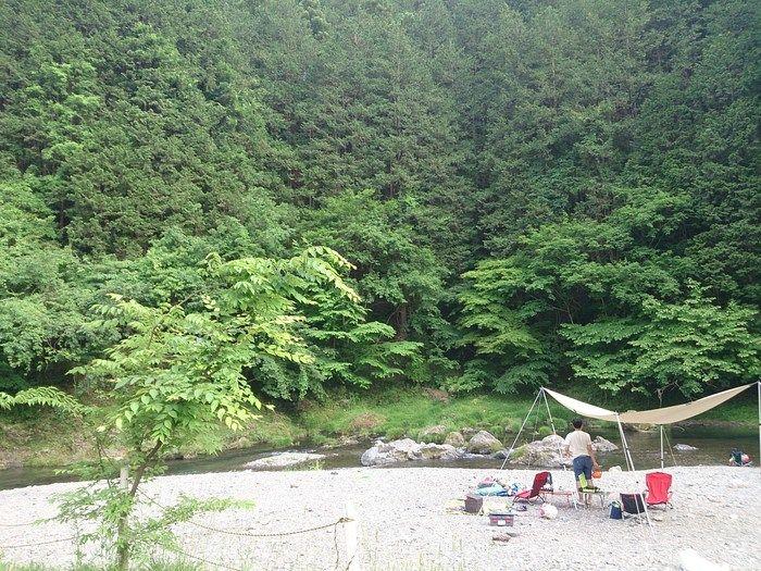 cazuキャンプ場の川辺でキャンプをする男性