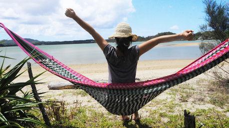 綺麗な砂浜でハンモックに乗り、手を空に伸ばしくつろぐ女性