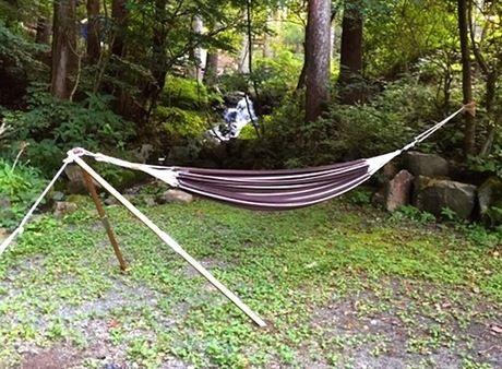 林間の川のほとりにハンモックスタンドを使ってハンモックを設営した様子