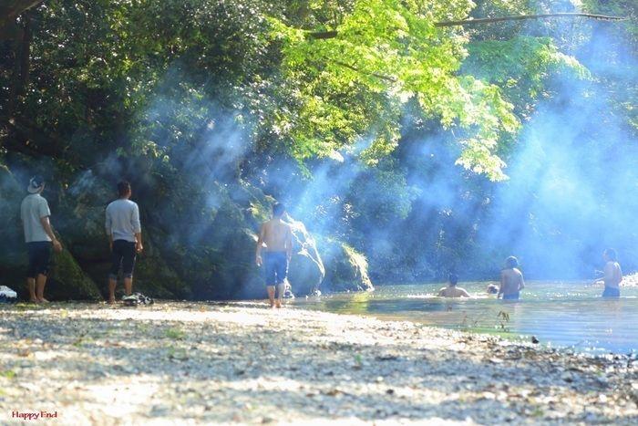 光が降り注ぐ中飯能河原で水遊びを楽しむ人々