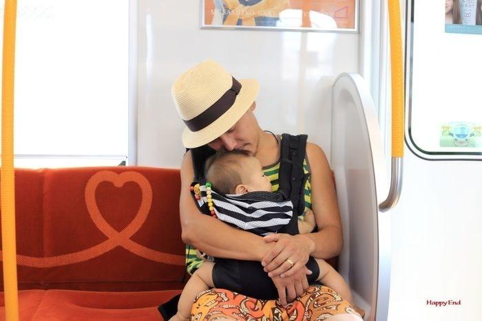 電車で赤ちゃんを抱きながら眠るお父さん