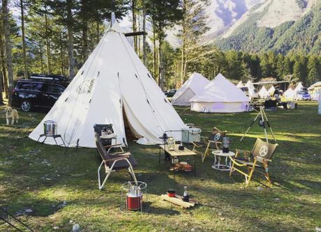 大自然の元でコットンテントを張りテントをする様子