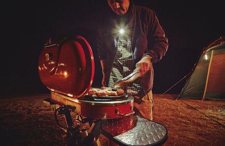 コールマンのヘッドランプをつけて肉を焼く様子