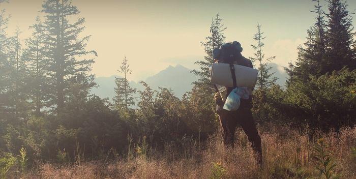 森林の中でシュラフを背負った男性