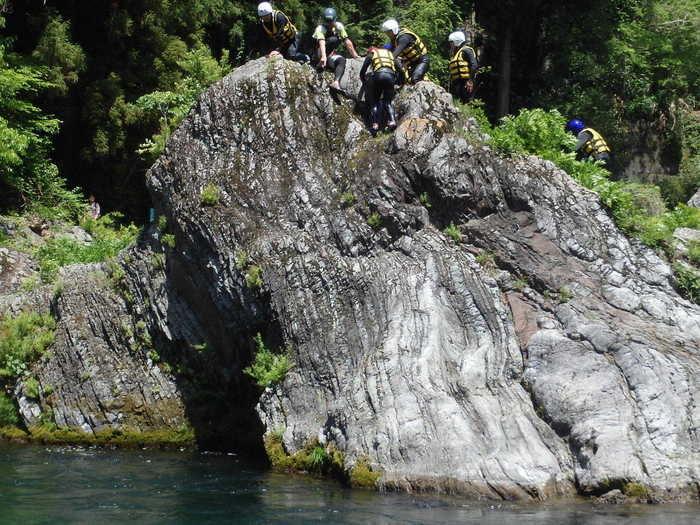飛び込むために岩に登る人