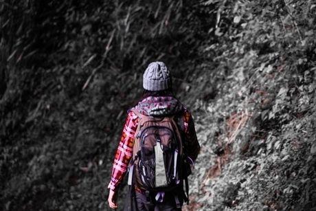 岩肌に向かって歩く女性の後ろ姿