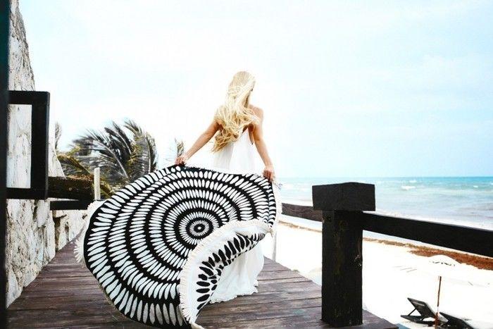 海辺でラウンドタオルを持つ女性