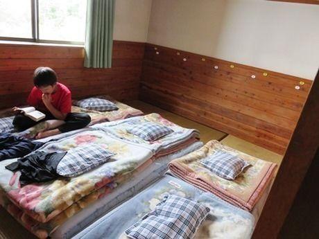 西穂高岳の山荘の寝室で本を読む子供