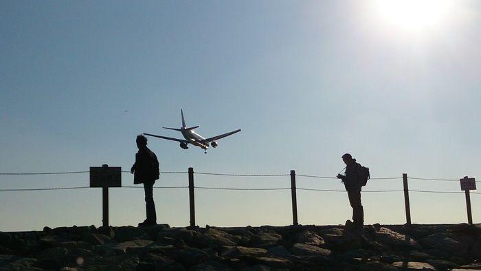 飛行機の後ろ姿を撮る男性の影