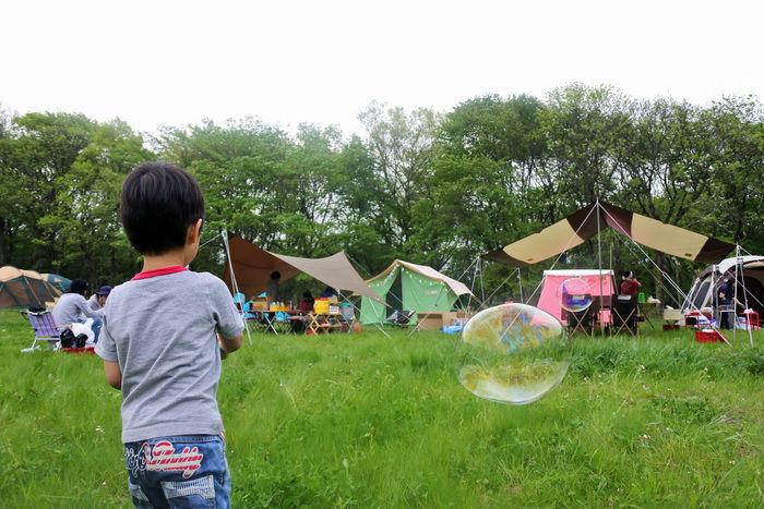 キャンプ場でシャボン玉をとばす男の子