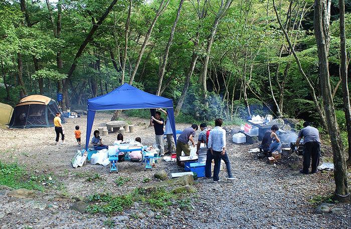 小滝沢キャンプ場で小さな淵が連なる花貫川と広葉樹に囲まれながら大人数でバーベキューを楽しむ様子
