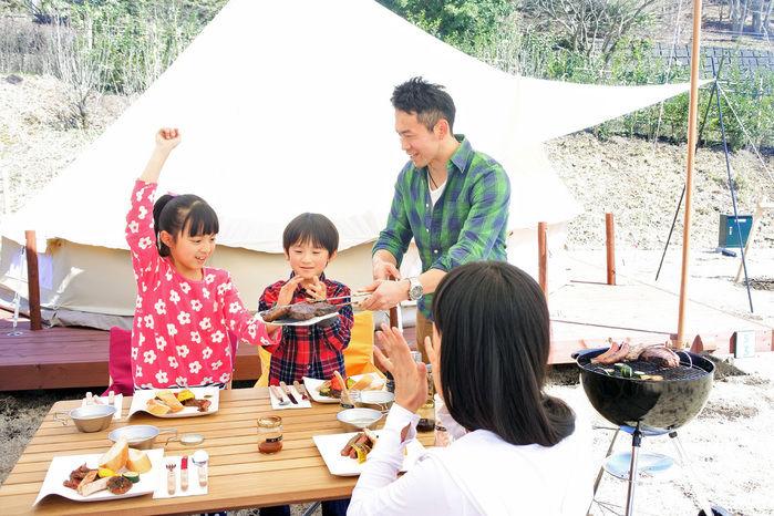 グランピングで食事を楽しむ家族