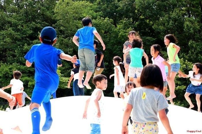 つつじ山広場の一角にある白い小山で跳ねる子供たち