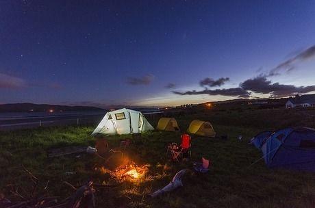 キャンプ場でたき火を囲む人々