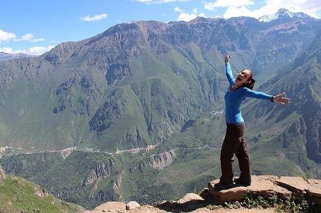 山の上で手を広げる女性