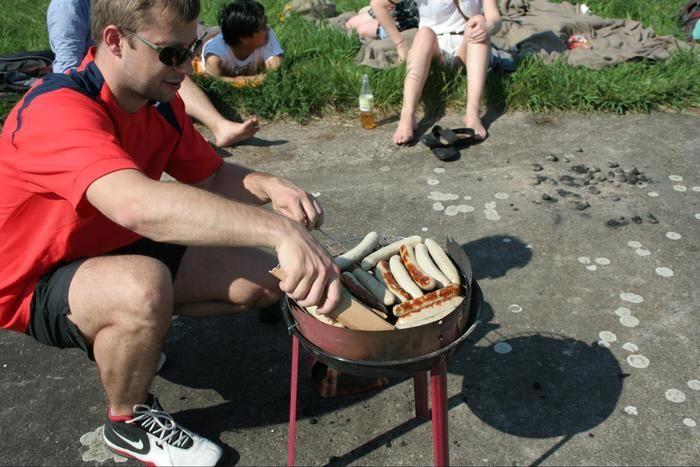バーベキューグリルでソーセージを焼く男性