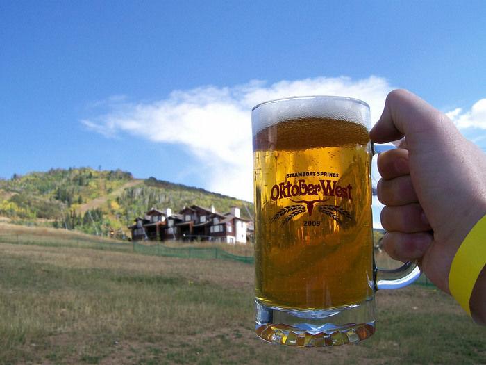 青空とログハウスを背景にビールジョッキを持つ手