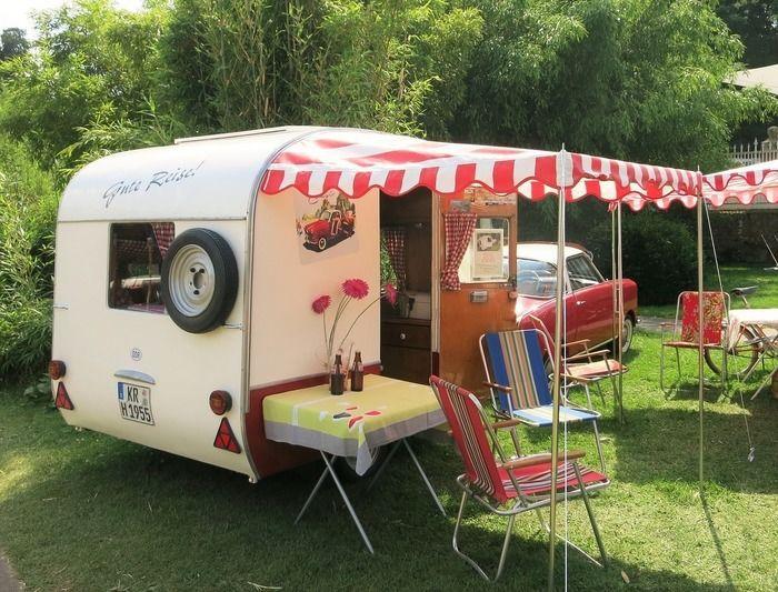 レトロなキャンピングカーを使ってキャンプをする様子