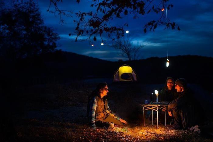 夜の山でテントを張って語り合う人々