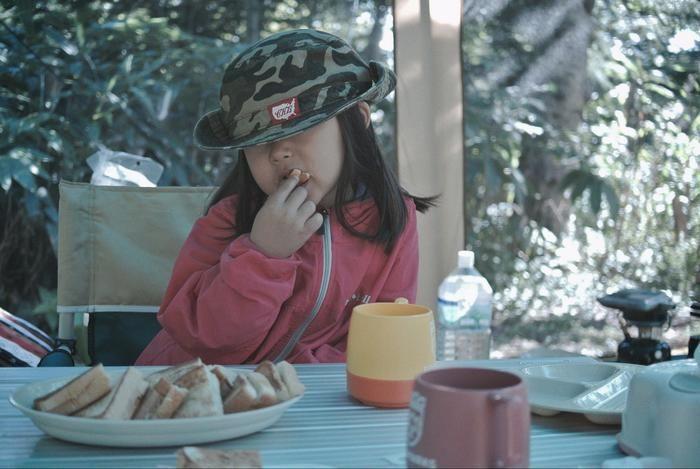 キャンプでサンドイッチを食べる女の子