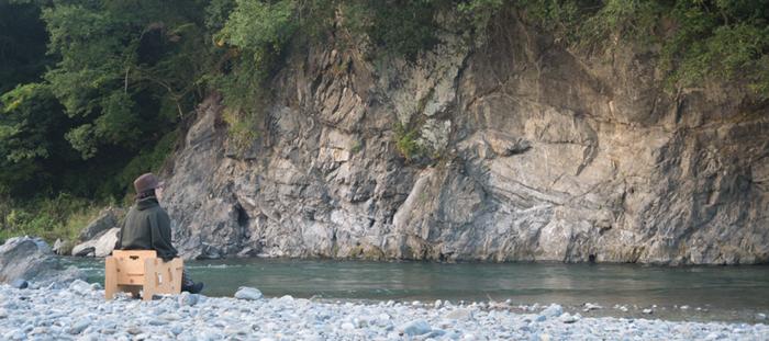自然の空気に溶け込む川沿いのチェア